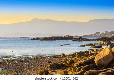 Rocky coast ans anchored boats in Arousa island at the evening with Curota mount at background