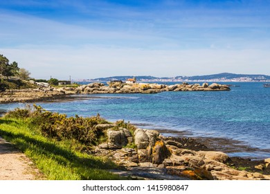 Rocky coast of Cabalo Point in Arousa Island with lighthouse on top