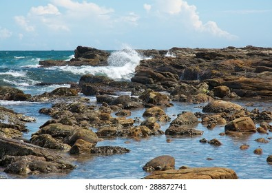Rocky coast landscape with metamorphic rocks and splashing foaming waves, Southern Province, Sri Lanka, Asia.