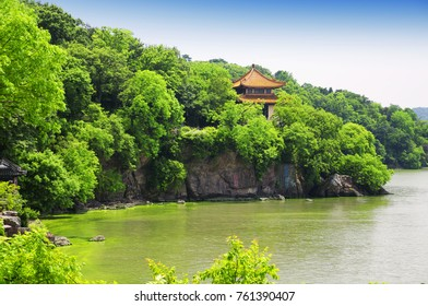 The rocky coast line of Taihu or Lake Tai scenic area in Wuxi China in Jiangsu province with an algae bloom near shore. a Chinese poem is on the rocky cliffs.