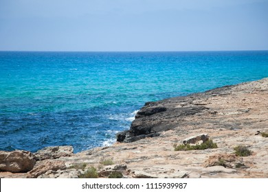 Rocky coastal landscape with a small cliff overlooking the open sea