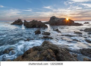 Rocky coastal sunset seascape with sunburst. This seascape was taken at sunset with sunburst peeking through the rocks.  This photo was taken at Corona del Mar, Newport Beach, California.