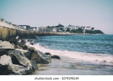 A rocky coastline and boardwalk on a wavy ocean