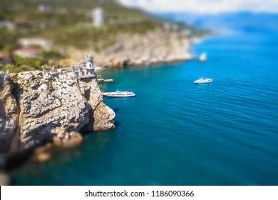 Rocky coastline with castle Swallow's Nest at the precipice, Crimea, Russia. Miniature tilt shift effect. Swallow's Nest is a famous landmark of Crimea. Aerial view of the Black Sea coast of Crimea.