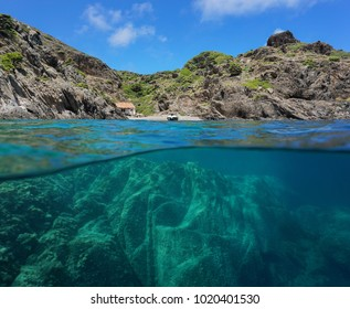 Rocky coastline with a cove and rock underwater, split view above and below water surface, Cap de Creus, Mediterranean sea, Spain, Costa Brava, Catalonia, Cala Gentil