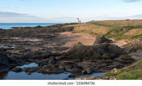 Rocky coastline east of Elie Ness and Elie Ness Lighthouse. Fife Coastal Path, Elie, Fife, Scotland.