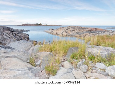 Rocky coastline, grass in the foreground, blue sea and distant island in the swedish archipelago