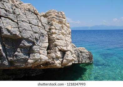 The rocky coastline of Levrechio beach at Loggos on the Greek island of Paxos.