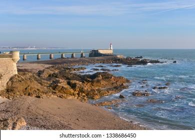 Rocky coastline and lighthouse at Les Sables d'Olonne, commune in the Vendée department in the Pays de la Loire region in western France