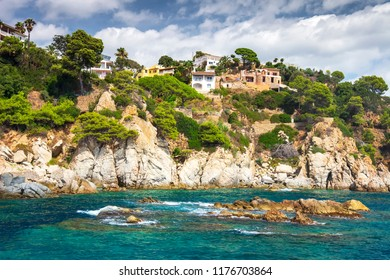 Rocky coastline in mediterranean in Lloret de Mar, Costa Brava, Spain with village houses on hills and mountain. Beautiful view on house on rocks on sea shore. Life in Mediterranean on summer day
