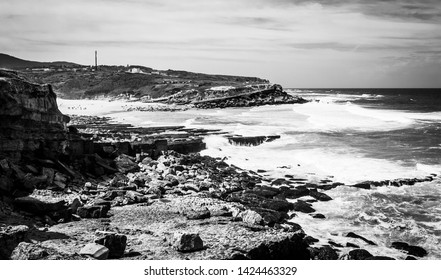 Rocky coastline of praia das maçãs in Portugal, taken from the rocks with cliffs and waves in the background. Taken in black and white.