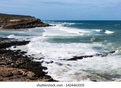 Rocky coastline of praia das maçãs in Portugal, taken from the rocks with cliffs and waves in the background.