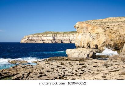 Rocky coastline and sea near collapsed Azure window in Dwejra Bay, Gozo island, Malta