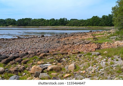 The rocky coastline of Stockton Harbor as the tide comes in with the Searsport shoreline in the distance.