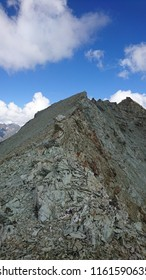 Rocky crest with gneiss pebbles and stones over Ignes Pass on a sunny Summer afternoon - Switzerland