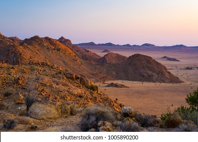 Rocky desert at dusk, colorful sunset over the Namib desert, Namibia, Africa, glowing rocks and canyon.
