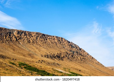 Rocky dry yellow cliff sloping down, against light blue sky, at Tablelands, Gros Morne National Park, Newfoundland, Canada. - Shutterstock ID 1820497418