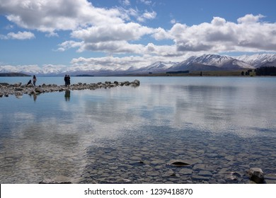 The rocky foreshore of Lake Tekapo, South Island, New Zealand with cloudy sky and reflections.