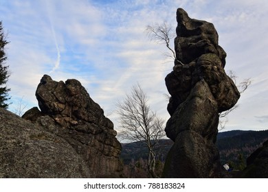 Rocky formation in Sudety mountains with beautiful sky and plane trails and clouds. Hiking in the mountains between peaks with stones on the top. Sport day recreation illustrated image of hills.