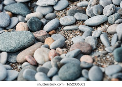 Rocky ground with a bed of sand in the bright sunlight. Looks like a hiking trail or path. Rocky beach or shoreline.