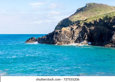 Rocky headland leading to the Atlantic Ocean on Cornwall's north coast with gentle waves breaking against the foot of cliffs
