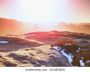 Rocky hill above inverse mist. Winter cold weather in mountains colorful fog. Misty valley in winter mountains.