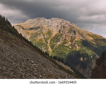 Rocky hill in Caucasus mountains with heavy stormclouds above the peak, Georgia