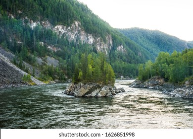 Rocky island covered by spurce trees in twilight. Confluence of the mountain rivers Balyiktyig hem and Kyzil hem, Siberia, Russia.