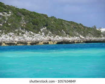 Rocky island covered in  lush greens with the different hues of blue waters of Exuma Cays, Bahamas. The islands are a popular destination for tourists.