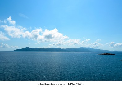 Rocky island in the distance over the beautiful blue sea