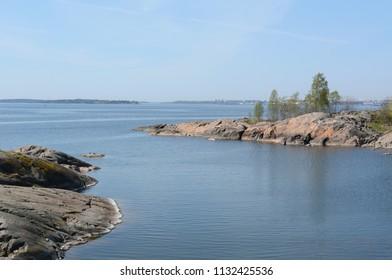 Rocky island shoreline and still deep blue water at Suomenlinna beach