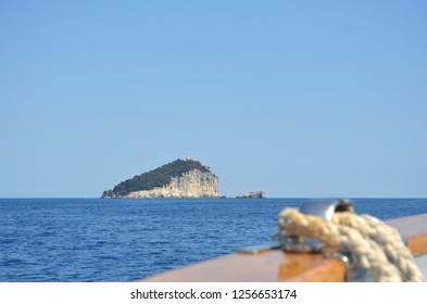 A rocky island, topped with forest, is surrounded by a calm ocean. A light house is on the peak. Rope and tackle on a boat are in the foreground. The sky is clear and pale blue.