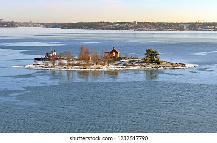 Rocky island with wooden house in Helsinki archipelago in sunny spring day. Suomi