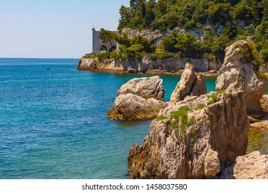 The rocky islands is in the blue water of the Adriatic sea. Big stones are in the middle of the sea not far away of green mountains and hanging castle above the sea water.