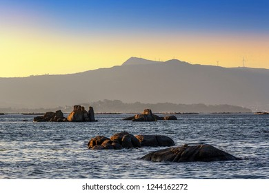 Rocky islets in Arousa Bay with Curota mount at background