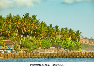 Rocky jetty protects the picturesque coastal town of Candidasa on the island of Bali in Indonesia with coconut palms in the background.