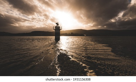 Rocky lake shores and lighthouse under the dark stormy evening sky after the rain. Dramatic cloudscape. Gare Loch, Rhu, Scotland, UK. Travel destinations, vacations, leisure activity concepts