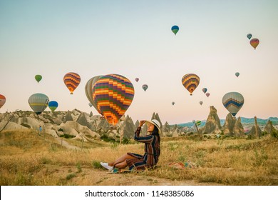 rocky landscape in Cappadocia, Turkey. Hot air ballooning in morning is most amazing attraction in Kapadokya during Sunrise, woman with hat watching hot air balloons