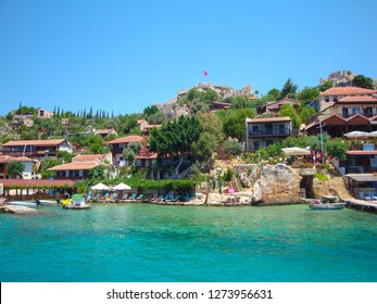Rocky landscape of Kalekoy village, the popular tourist location in Kekova bay, famous for idyllic cafes and cottages.  Cafe at sea coast, near ruins of the ancient city on the Kekova island.