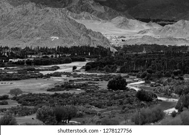 Rocky landscape of Kargil with himalayan mountains in background , green valley , Ladakh, Jammu and Kashmir, India. Black and white image.
