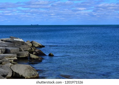 Rocky limestone breakwater and very calm waters on Lake Michigan with clouded sky.