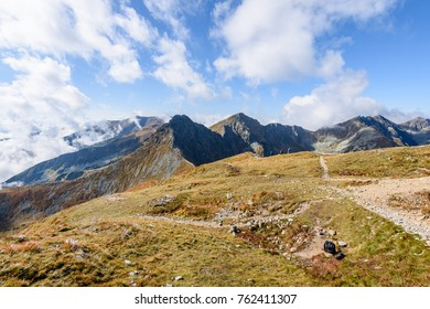 rocky mountain peak area view in slovakia. bright sunlight and white clouds on blue sky covering hills. panoramic view