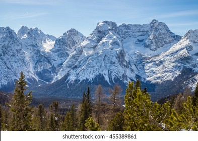 Rocky mountain peaks seen over pine trees in the Dolomites, Italian Alps