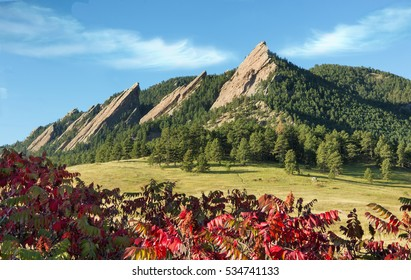Rocky Mountain Scenic Boulder Flatirons. Red Sumac Fall Foliage in Foreground. Wispy Clouds Above Mountains.