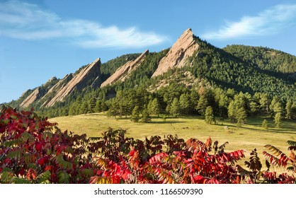 Rocky Mountain Scenic Flatirons with Fall Colors. Autumn in Boulder, Colorado. Red leaves in foreground. Mountain Rock Cliffs in background, surrounded by hiking trails, nature & trees in park.