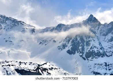 rocky mountain in the snow and clouds