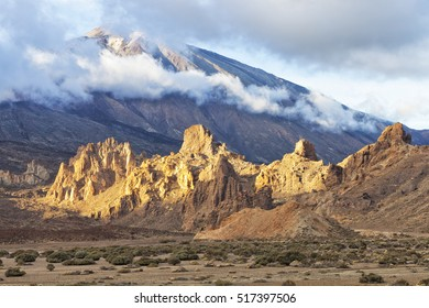 Rocky mountain tops glowing in sunset light at the foot of volcano El Teide covered with low clouds in Tenerife national park