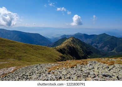 rocky mountain tops with hiking trails in autumn in Slovakian Tatra western Carpathian with blue sky and late grass on  hills. Empty rocks in bright daylight, far horizon for adventures.