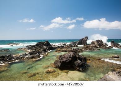 Rocky ocean coast with waves in Maui, Hawaii