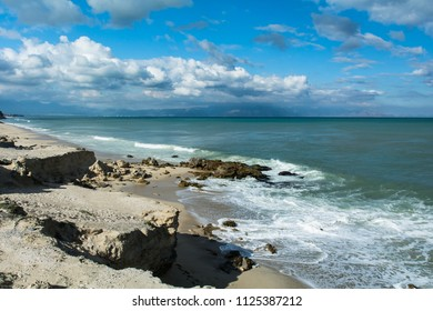 Rocky ocean shore line with blue cloudy skies and green blue blanket sea